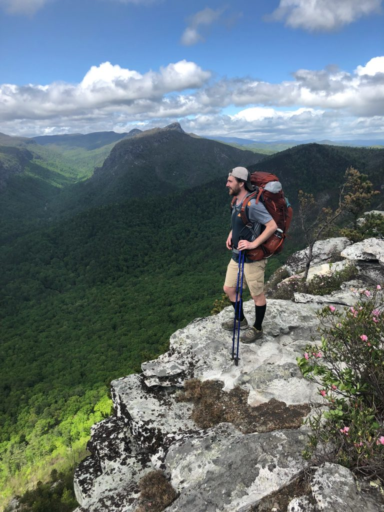Dr. Consla standing on a rock looking out over a cliff with green vegetation below while wearing a hiking backpack