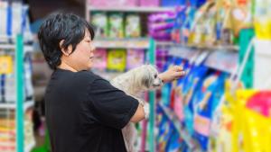 woman in pet food store choosing food for dog